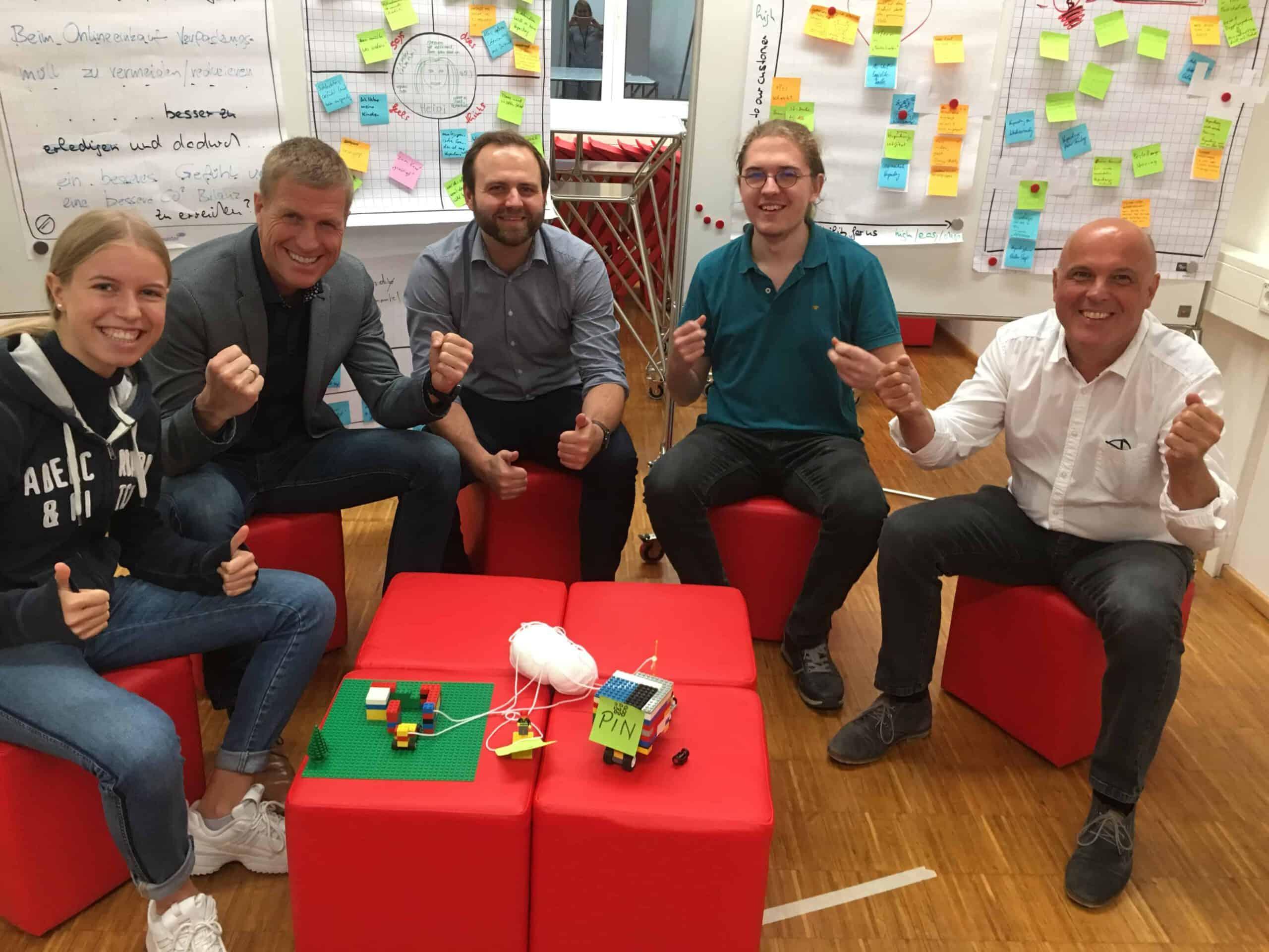fuenf glueckliche Dsign Thinking Teilnehmer mit Prototyp